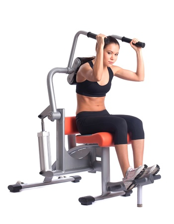 sporty woman doing exercises on gym equipment, isolated on white photo