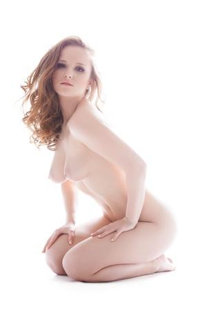 mujer desnuda sentada: Retrato de cuerpo entero de la mujer desnuda bonita que se sienta en el suelo aislado en blanco Foto de archivo