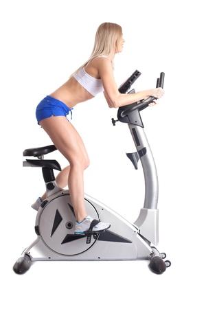 sportswear: Athletic blonde training on bike exerciser, isolated on white Stock Photo