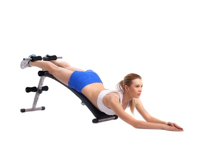 Young woman shakes press on exerciser, isolated on white photo