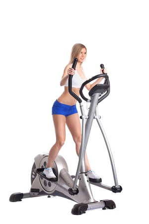 Slim blonde practicing on trainer, isolated on white photo