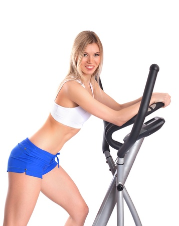 Slim woman leans on gym equipment, on white background photo