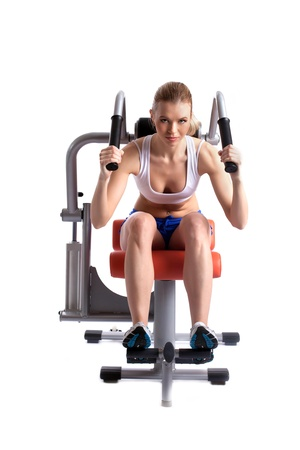 Athletic woman on hydraulic trainer, isolated on white photo