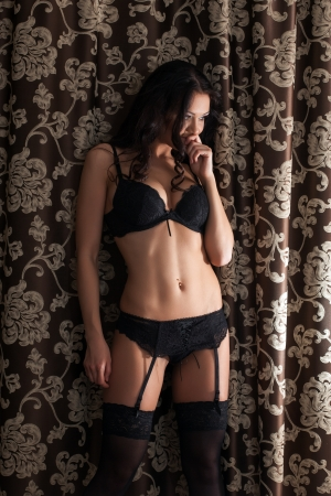 provocative women: Curly slender brunette posing in black lingerie on curtains background