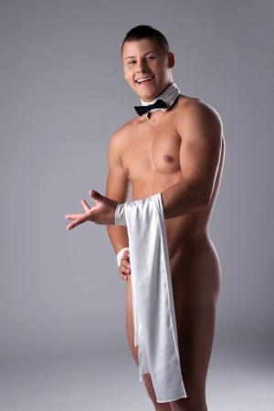 naked male body: Smiling naked guy with waiter s napkin, on gray background Stock Photo