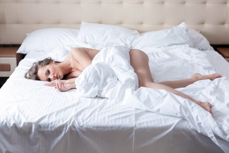 nude in bed: Beautiful slim girl posing naked in hotel bed Stock Photo