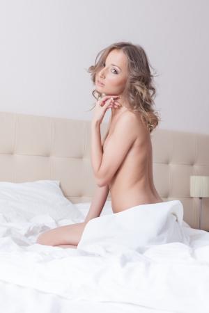 mujer desnuda sentada: Encantadora mujer desnuda sentada en la cama de hotel, close-up Foto de archivo