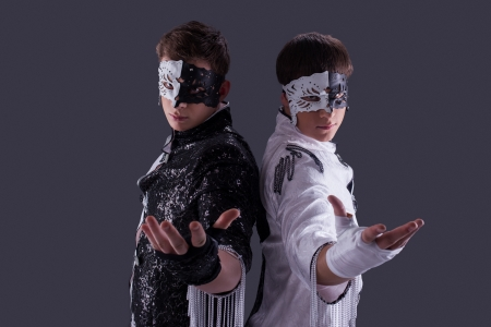 Portrait of attractive young guys in masks, on gray background photo
