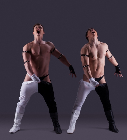 Handsome strippers taking off pants, on gray background photo