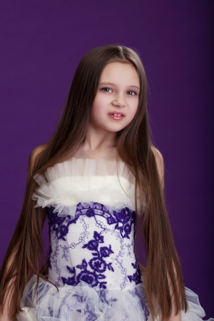 Portrait of beautiful little girl with long hair, on purple background photo