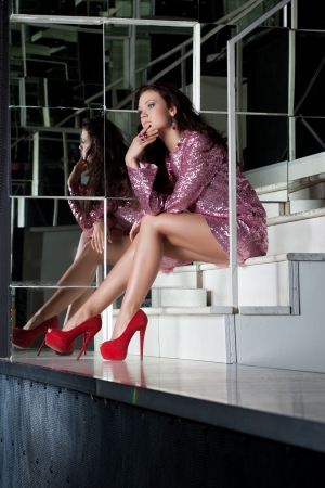 Full length portrait of Beauty woman in fashion pink dress on stairs photo