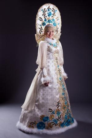 russian woman: Smiling woman in Russian costume and kokoshnik on gray background