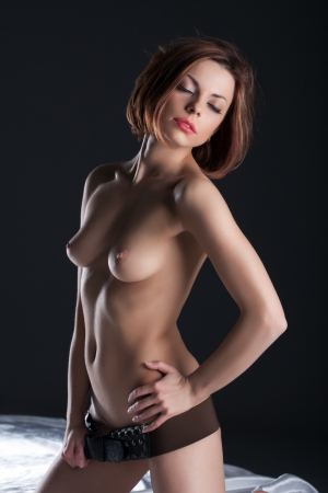 seins nus: Séduisante brunette aux seins nus posant dans la ceinture en cuir, sur fond gris Banque d'images