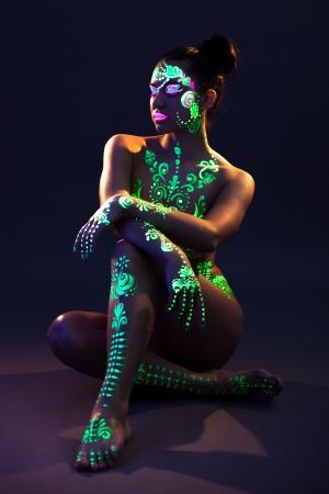 Image of slim girl with UV glowing makeup posing in dark Reklamní fotografie