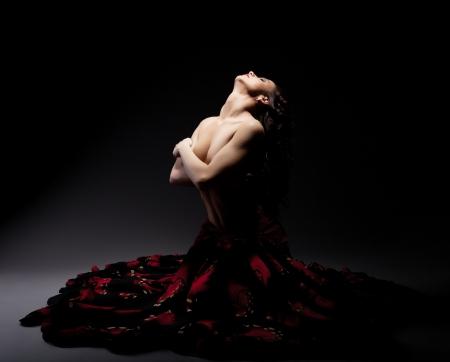 Beautiful topless woman posing in flamenko skirt, on black background photo
