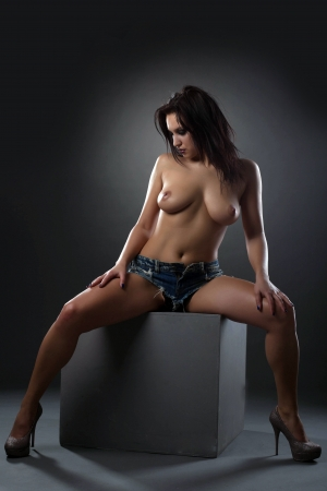 female breast: Hot topless woman sitting on cube in studio Stock Photo
