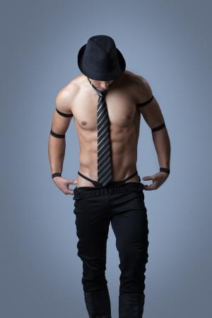 lazo negro: Individuo muscular hermoso quitarse la ropa en el estudio Foto de archivo
