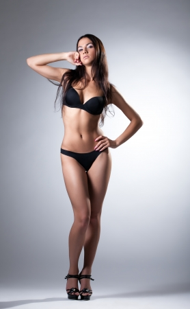 Young slim model posing in black lingerie, on gray background photo