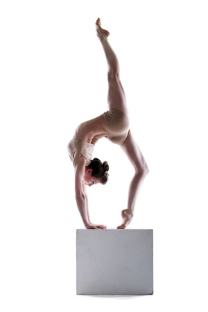Slim woman balancing on cube in studio, isolated over white background Stock Photo - 19356649