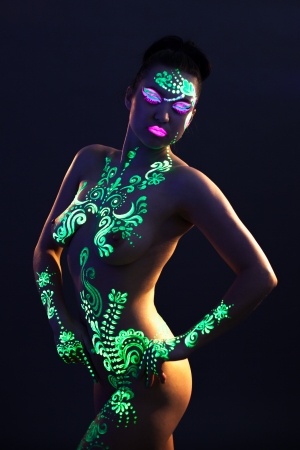 nude art model: Portrait of sexual woman with UV glowing makeup, close-up