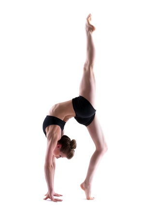 young gymnast: Young flexible brunette posing in studio, isolated on white