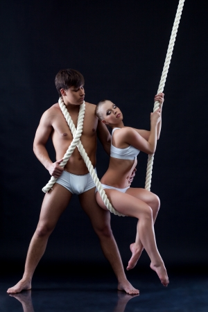Pair of young aerialists posing with rope, on dark background photo