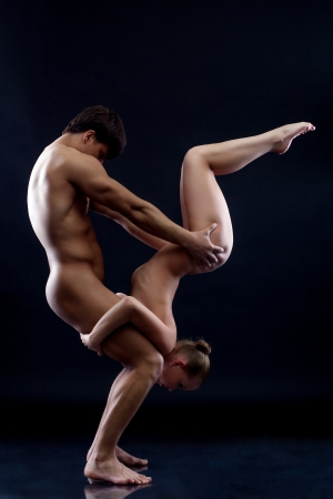 nude sport: Young naked gymnasts showing trick in studio, on dark background