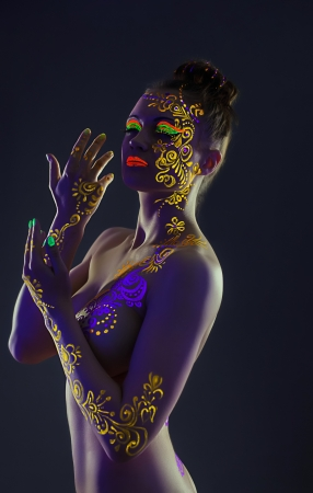 Elegant model with yellow UV pattern on body, close-up photo