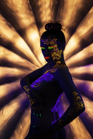 Portrait of attractive naked woman with UV makeup, close-up photo