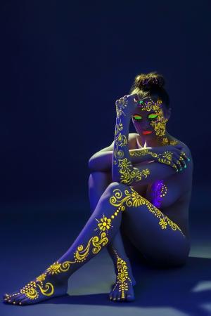 body paint: Modelo agraciado posando con el patrón ULTRAVIOLETA amarilla en el cuerpo Foto de archivo