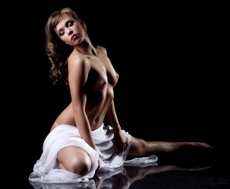 mujer desnuda senos: Elegante morena posando en topless en el estudio, aislados en negro Foto de archivo