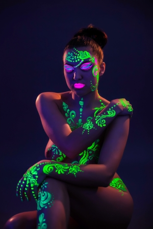 Naked woman posing with colorful UV makeup, close-up photo