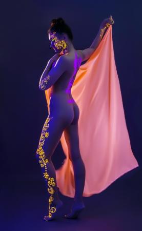 body paint: Modelo delgado con maquillaje UV posando en el estudio, primer plano
