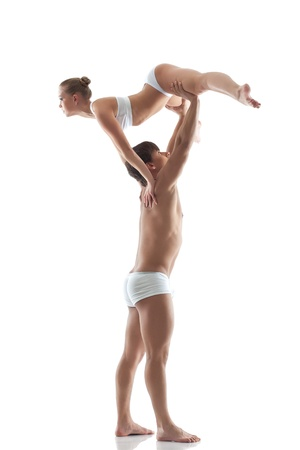 boy gymnast: Gym support in performance of two young acrobats, isolated on white