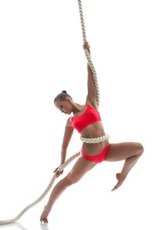 acrobacia: Mujer agraciada colgando de una cuerda en el estudio, aislado más de fondo blanco Foto de archivo