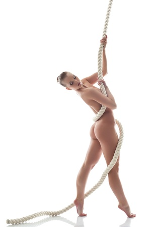 nude gymnast: Pretty nude model posing with rope in studio, isolated on white