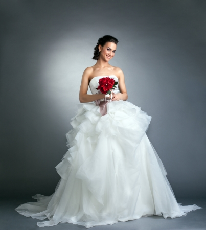 Charming bride with bouquet posing in studio, on gray background