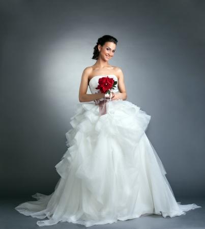 hochzeitsfrisur: Charming Braut mit Blumenstrau� posiert im Studio, auf grauem Hintergrund