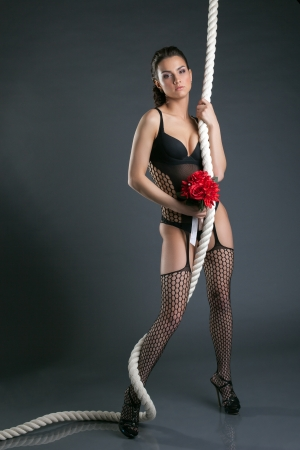 Attractive model posing with rope and bouquet, on gray background photo