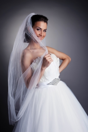 hairdo: Portrait of smiling bride hiding behind veil, close-up