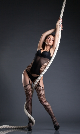 Image of hot slender woman posing with rope, close-up photo