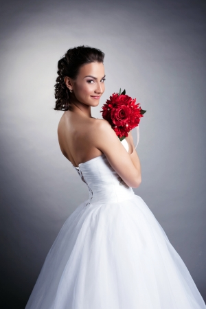 Portrait of attractive bride posing with bouquet, close-up photo