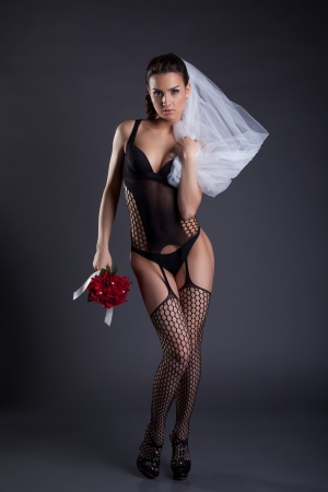 Sexy bride posing in black lingerie and veil, on gray background photo