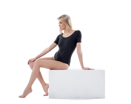 female stripper: Sensual young blonde posing sitting on cube, isolated over white background