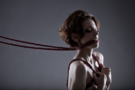 Passionate red-haired model tied with rope, close-up photo