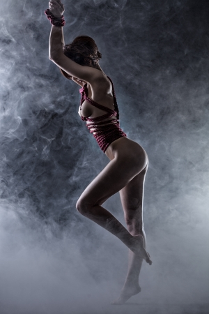 Graceful nude woman tied with rope in studio, on smoke backdrop