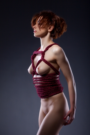 Naked red-haired woman bound in studio, close-up