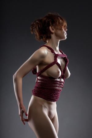 erotico: Giovane donna nuda sottile in posa con corda rossa, su sfondo grigio