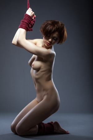 Young flexible nude woman posing tied with rope, close-up