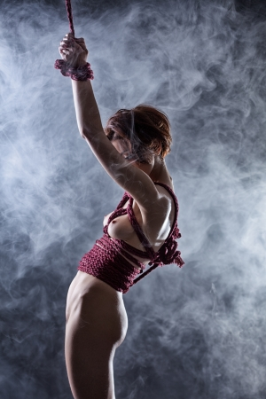 Sexual bound woman posing in studio, on smoke background